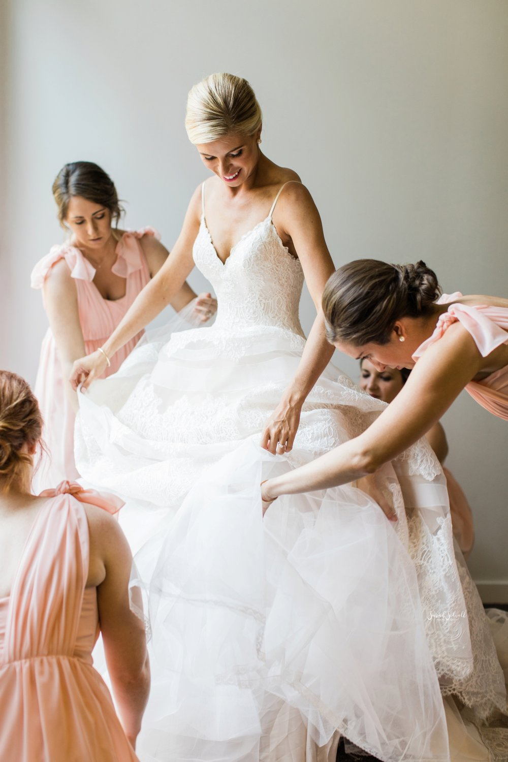 A bride gets into her wedding dress before her ceremony.