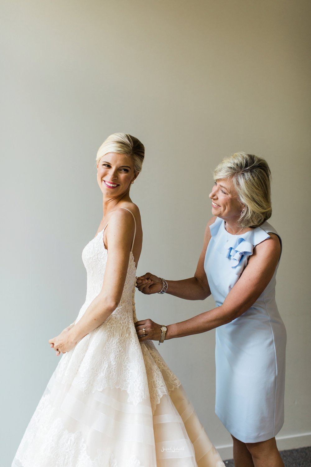 A bride's mother helps her to get into her wedding dress.