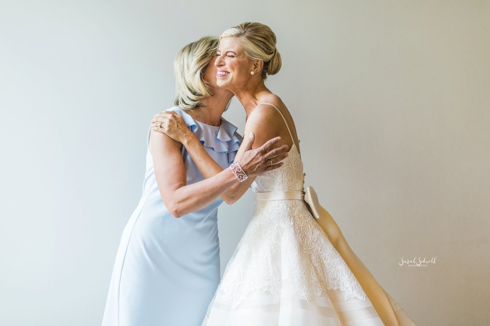 A mother kisses her daughter on the cheek before her wedding.