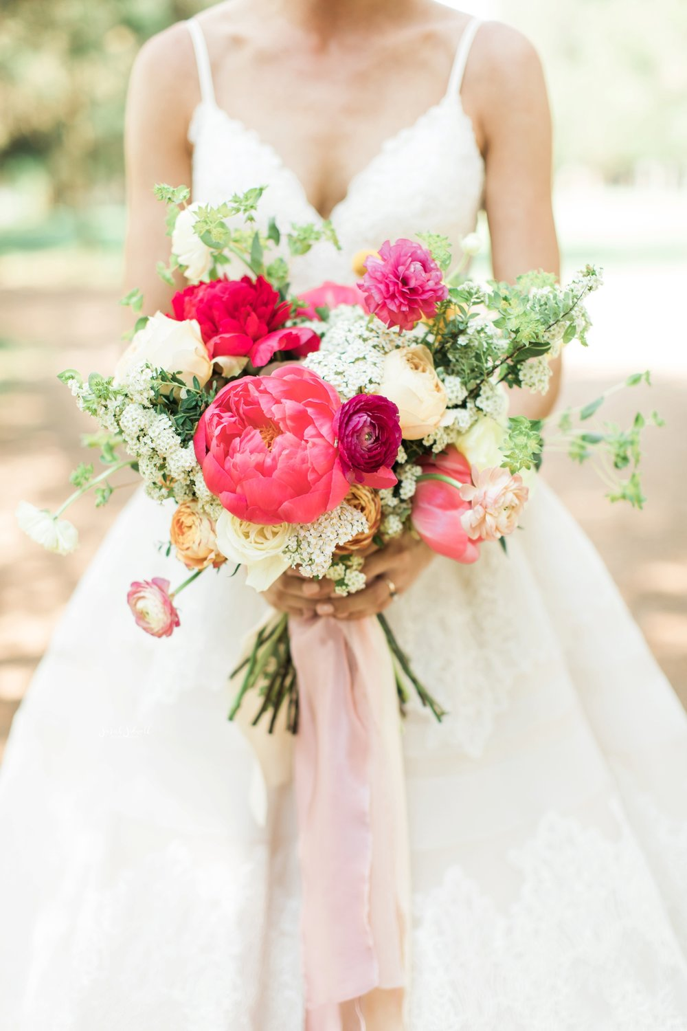 A bride holds her bouquet that has bright pink flowers.