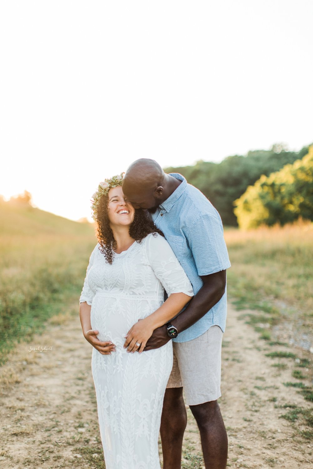 A man hugs his pregnant wife during a family maternity session.