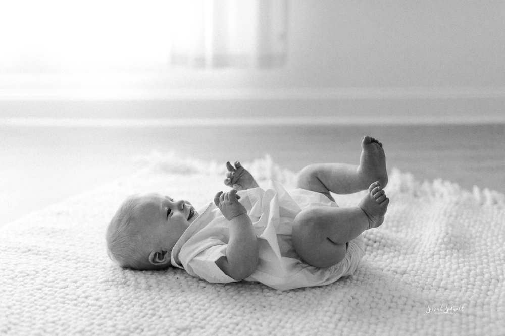 A baby lays on his back on the floor.