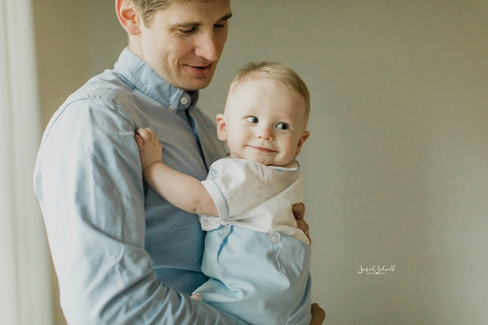 A baby pushes off of his father's chest to turn around.