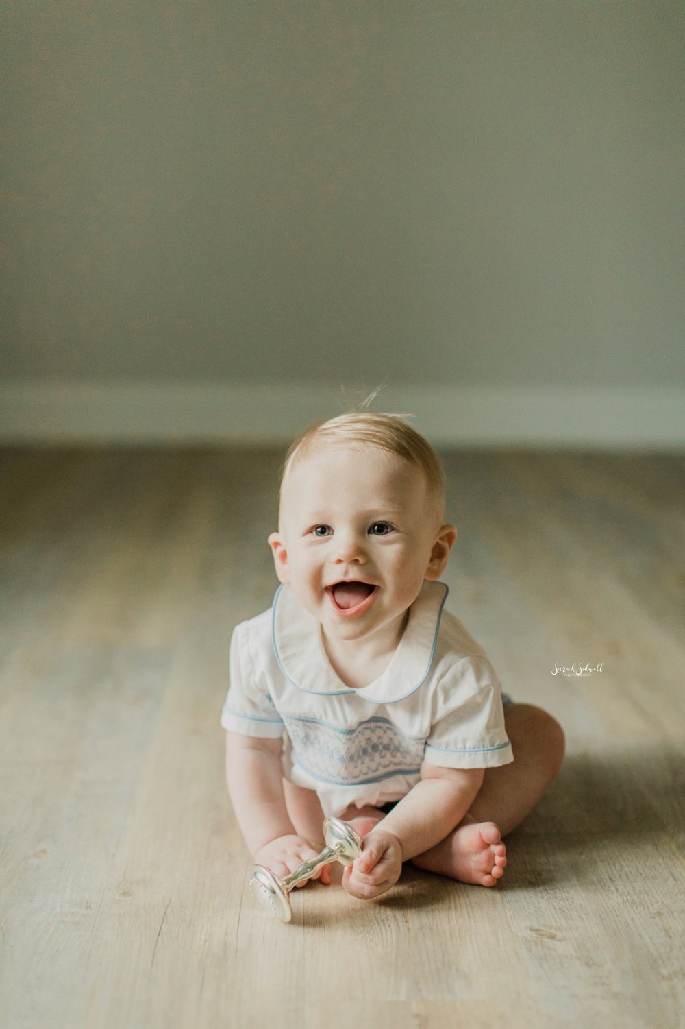 A baby sits up on a wooden floor and smiles.