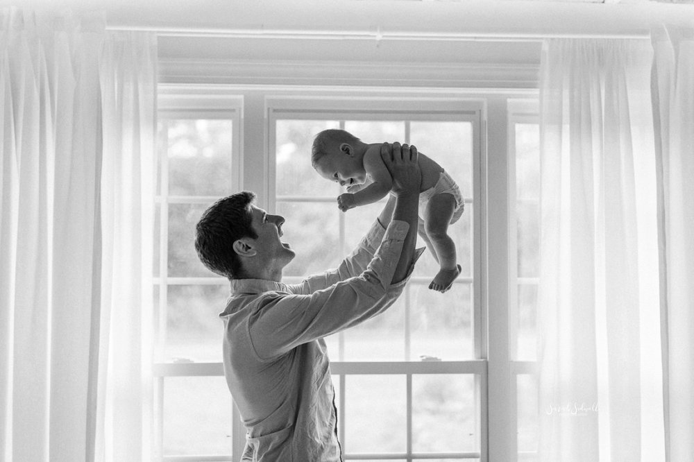 A father holds his baby in the air.