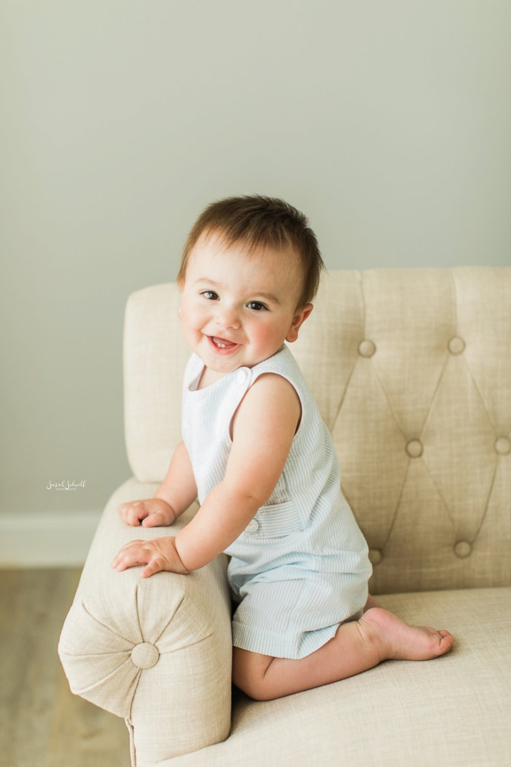 A baby sits on his knees in a white chair.