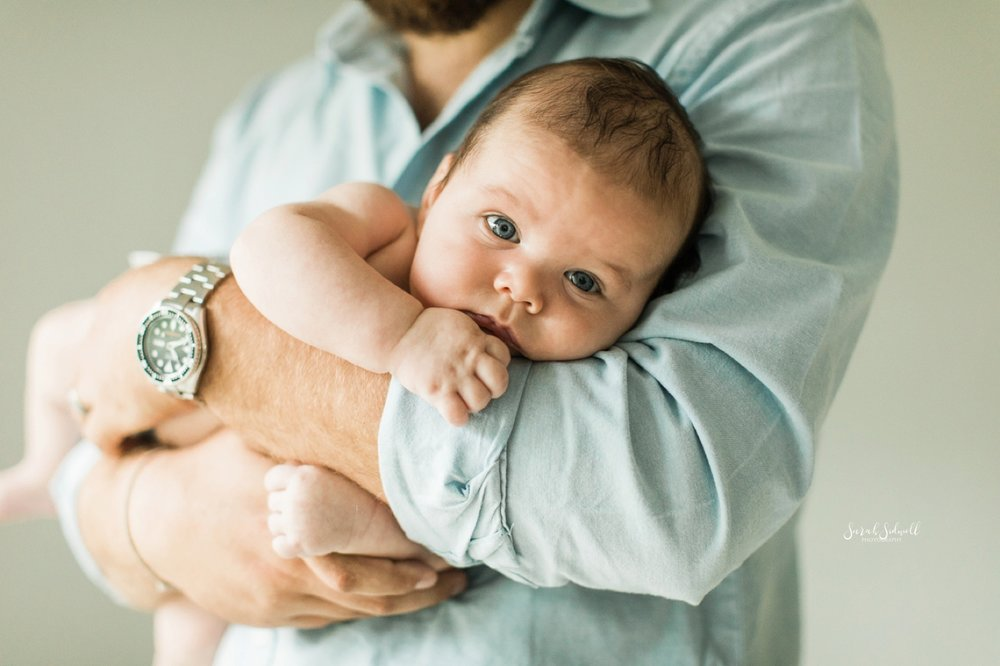 A dad rocks his baby in his arms.