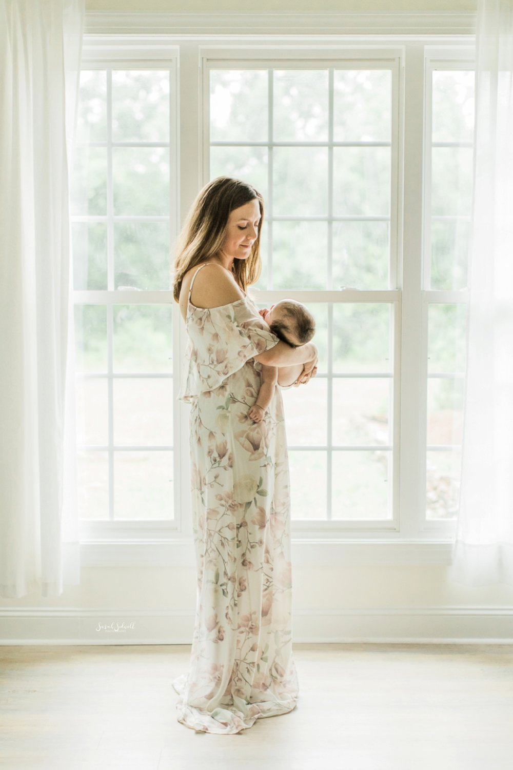 A new mother rocks her baby gently by a bright window.