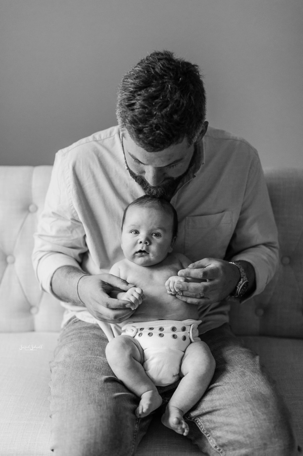 A father sits on a bed with his baby in his lap.