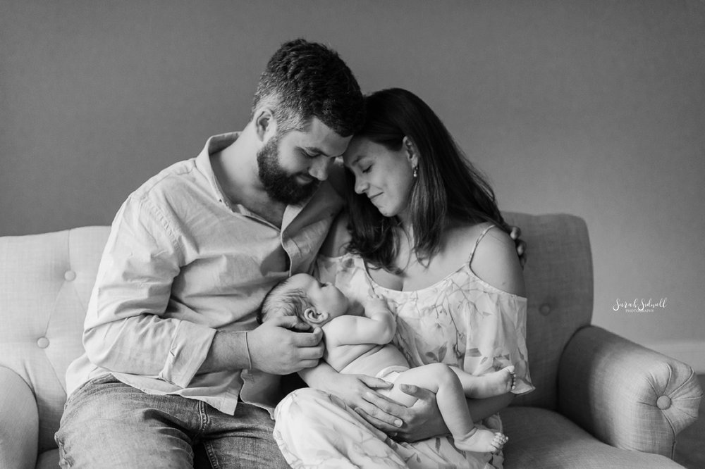 Two parents sit together, rocking their baby boy.