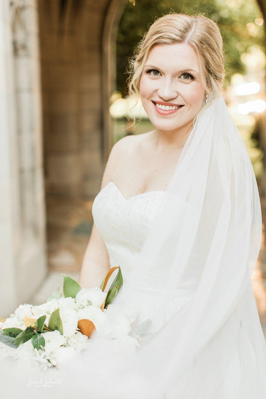 A bride's veil covers her torso.
