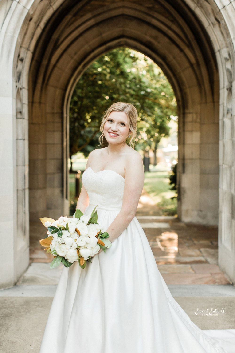 A bride stands under an arch holding her flowers.