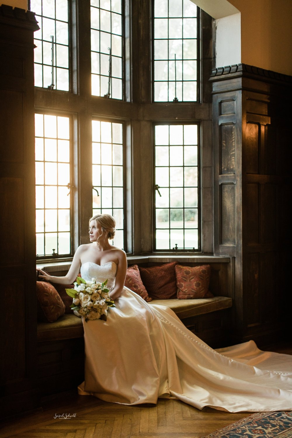 A bride sits in the sun next to a large window.
