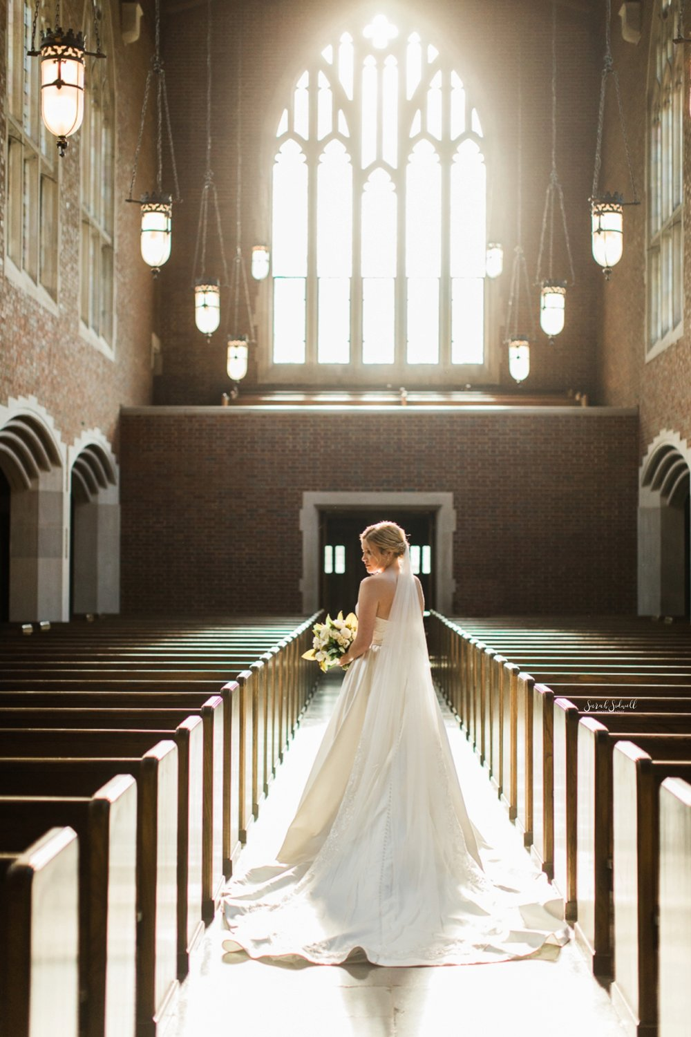 A bride stands in the aisle of a church.