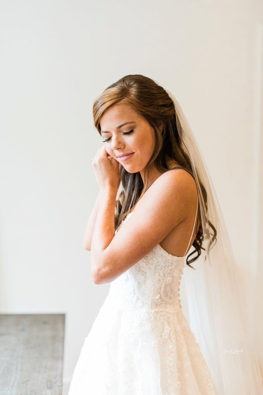 A bride puts her earrings in.