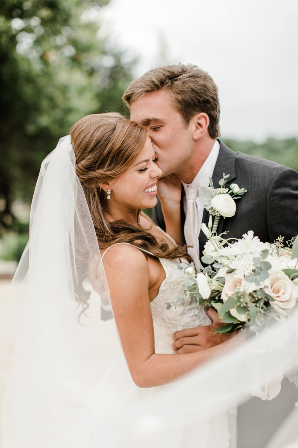 A groom kisses his bride on the cheek.