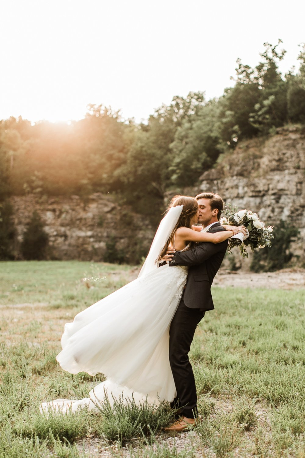 A bride jumps into the arms of her groom.