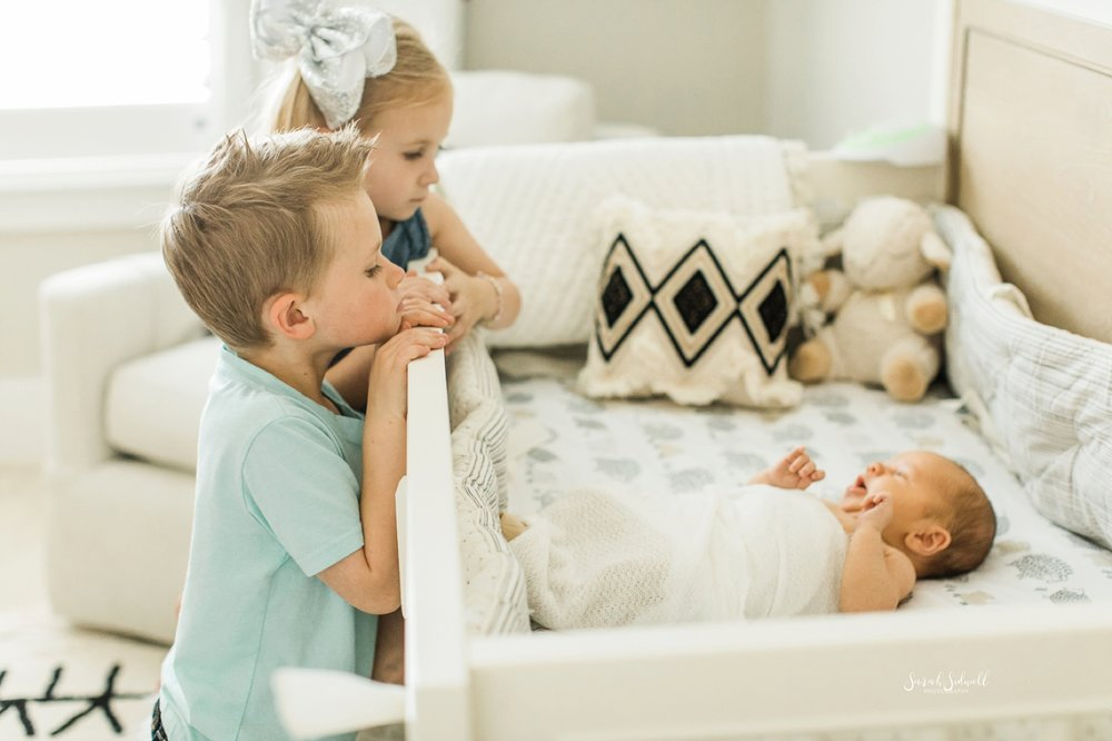 Two siblings look down at their new baby brother.