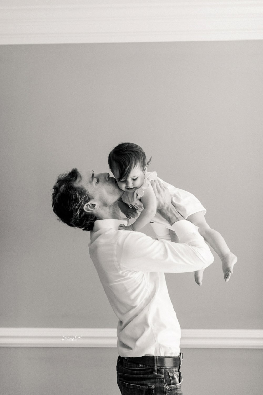A dad kisses his daughter on the cheek.