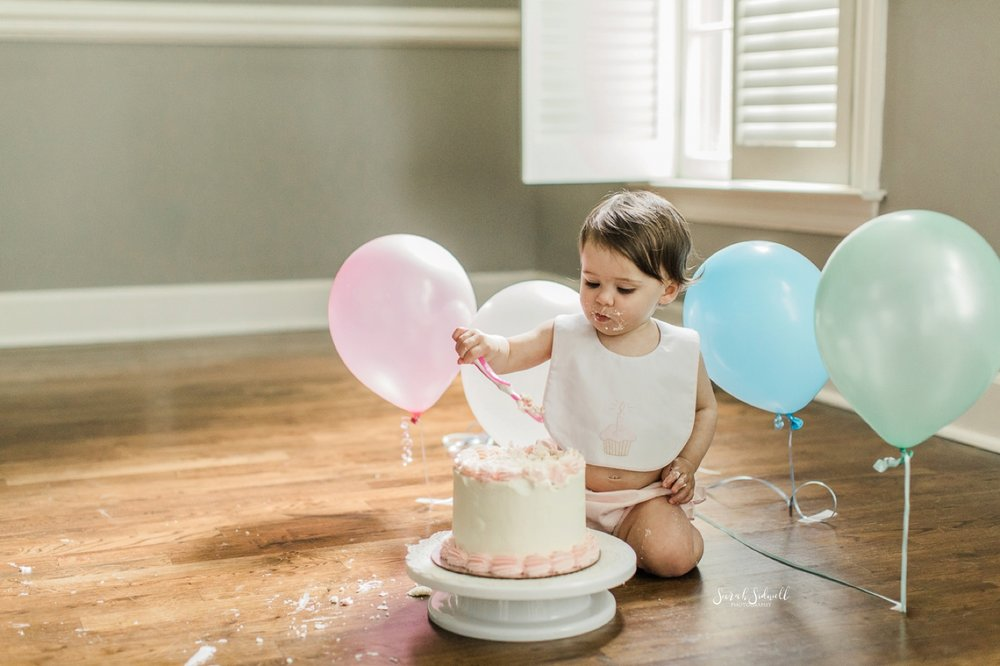 A baby girl smashes her first birthday cake.