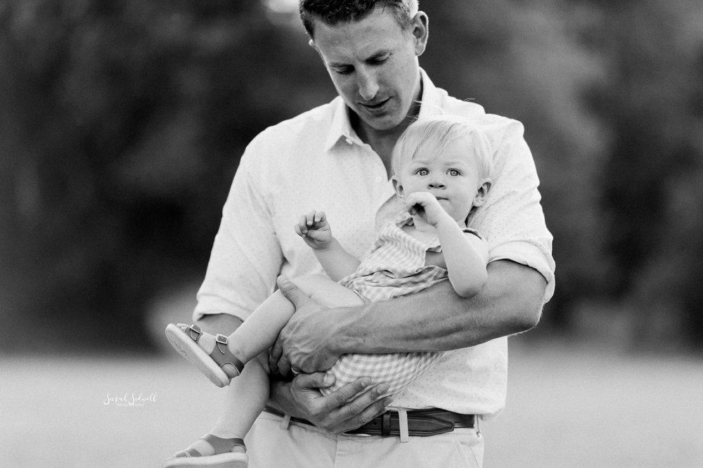 A father cradles his son in his arms.