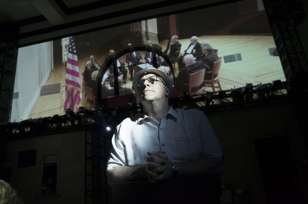 "Actor Michael Puzzo watches the film ""Behind Closed Doors."" Live performance and projection were thoroughly integrated in the installation. Credit: Tony Gerber"