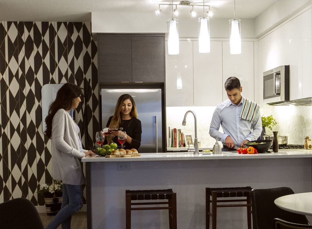 Friends gathering in a beautiful modern kitchen by Slokker Homes