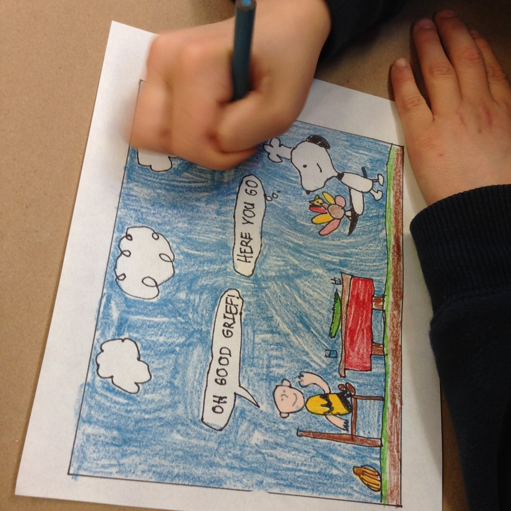 Aaron adding the finishing touches of blue to his Peanuts cartoon.