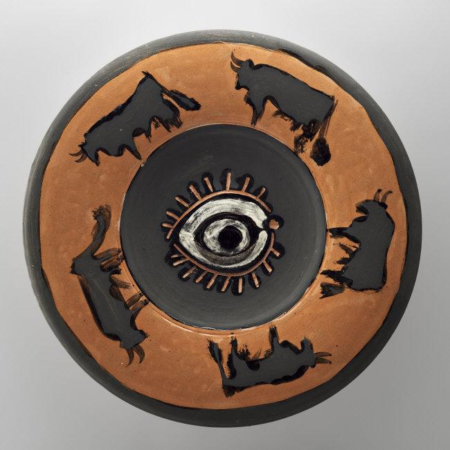 Pablo  Picasso, (1881-1973) © ARS, NY    Spanish Dish Decorated with an Eye and Bulls . 1957. Red terracotta, incised, partially covered, painted with clay engobe, ceramic, diam. 40 cm. MP3741. Photo: Mathieu Rabeau.    Location:   Musee Picasso, Paris, France    Photo Credit:   © RMN-Grand Palais / Art Resource, NY    Image Reference:   ART523442