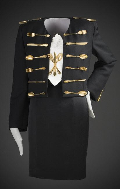 Moschino, Franco (1950-1994)   'Dinner Jacket' Ensemble, autumn/winter 1989-1990. Wool, wool and acetate, linen, and metal flatware. a) Jacket center back length: 18 1/2 in. (46.99 cm); b) Dress center back length: 27 1/2 in. (69.85 cm); c) Napkin (folded): 12 x 5 in. (30.48 x 12.7 cm). Los Angeles County Museum of Art, Gift of Leslie Prince Salzman (M.2005.82.1a-c)    Location:   Los Angeles County Museum of Art, Los Angeles, California, U.S.A.    Photo Credit:   Digital Image © [year] Museum Associates / LACMA. Licensed by Art Resource, NY    Image Reference:   ART482427