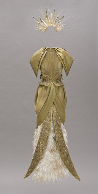 Woman's Gown with Accessories from the 'Fra Angelico Collection'. Kate Mulleavy (United States, born 1979). Laura Mulleavy (United States, born 1980). Rodarte LLC (United States, California, Los Angeles, founded 2005). United States, 2011. Metallic satin with feathers, metal sequins with wire, beads, and woven metallic ribbon. a) Gown: 66 in. (167.64 cm) nape to hem; b) Belt: 7 1/4 x 22 x 12 1/2 in. (18.41 x 55.88 x 31.75 cm); c-d) Panel detail: 63 1/2 x 9 1/2 in. (161.29 x 24.13 cm). Gift of Rodarte (Kate and Laura Mulleavy), Maria Arena Bell, Susan Casden, Eva Chow, DNA Boutique, Allison Sarofim, Karyn Silver, Christine Suppes, Lizzie Tisch, Dasha Zhukova and an Anonymous Donor (M.2012.147.10a-e)    Location:   Los Angeles County Museum of Art, Los Angeles, California, U.S.A.    Photo Credit:   Digital Image © [year] Museum Associates / LACMA. Licensed by Art Resource, NY    Image Reference:   ART483665
