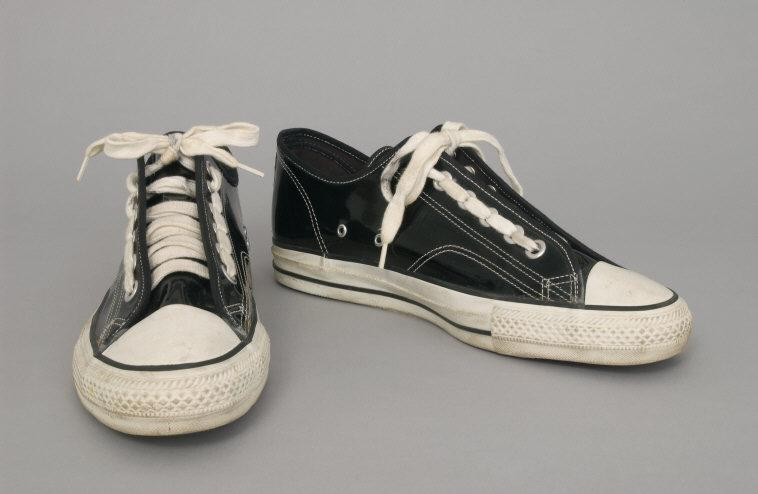 Designed by Rei Kawakubo, Japanese, born 1942. Comme des Garçons, Tokyo, 1969 - present. Worn by John Cale, Welsh, born 1942. Man's Patent Leather Sneakers. c. 1990s. Black patent leather, white rubber. Length: 11 1/2 inches (29.2 cm). 125th Anniversary Acquisition. Gift from the private collection of John Cale, 2002.    Location:   Philadelphia Museum of Art, Philadelphia, Pennsylvania, U.S.A.    Photo Credit:   The Philadelphia Museum of Art / Art Resource, NY    Image Reference:   ART499769