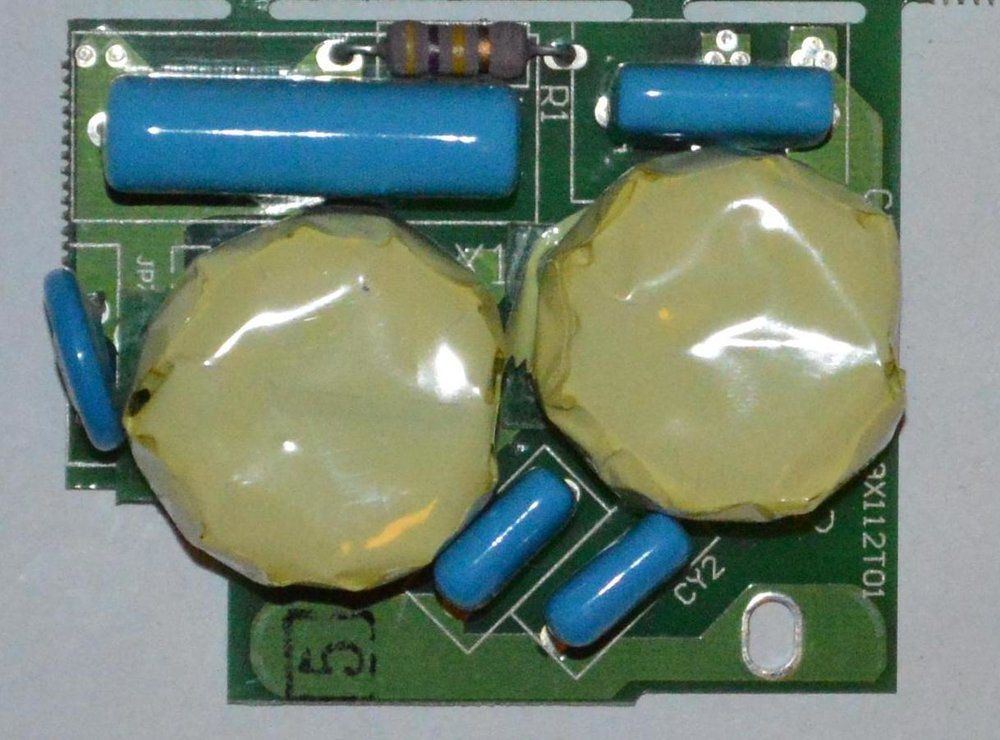 Input filter to the rectifier. The two yellow bodies contains the common mode input chokes. The blue component to the left is a metal oxide varistor to protect the input from overvoltage. The other blue components are various sizes of capacitors.