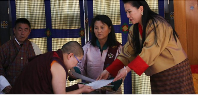 Tashi and her majesty Gyalyum Tshering Yangdon Wangchuck awarding a certificate to a participant.