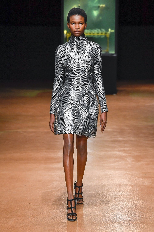 Laser cutting creates a ripple effect on silver stretch fabric.