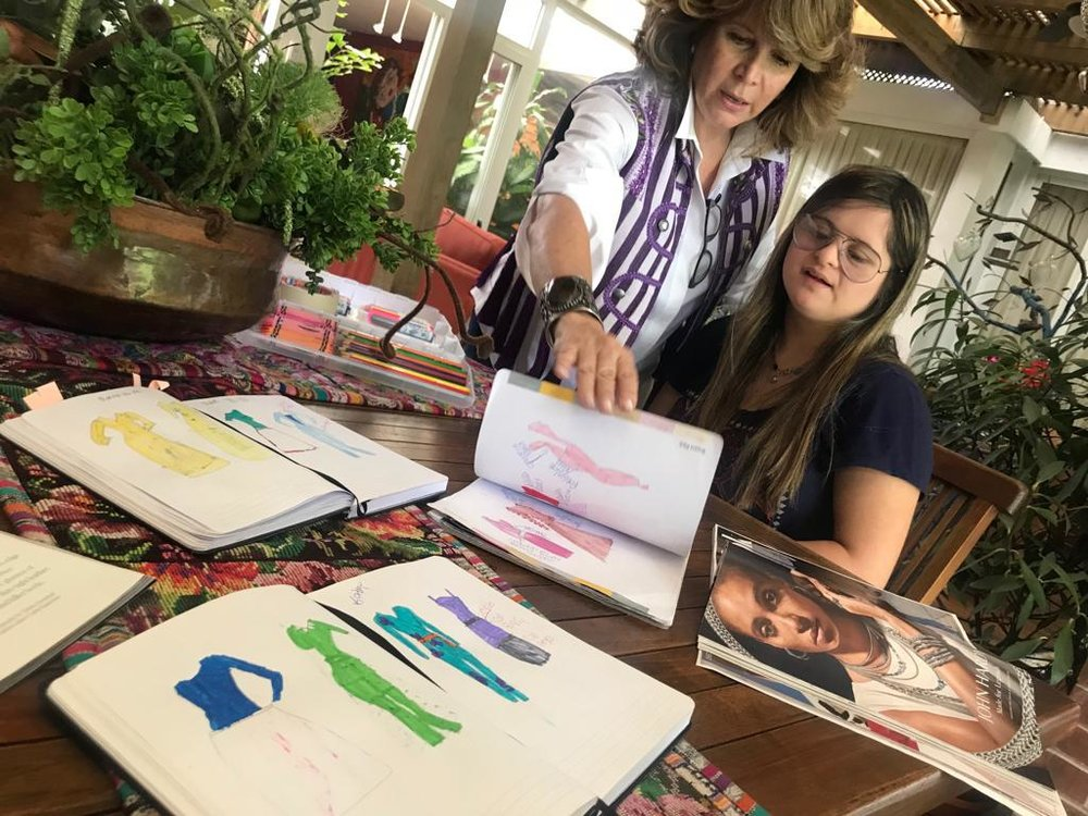 """Isabella goes through sketches at home in Guatemala City, with her mother, Isabel, who goes by """"Bel""""."""