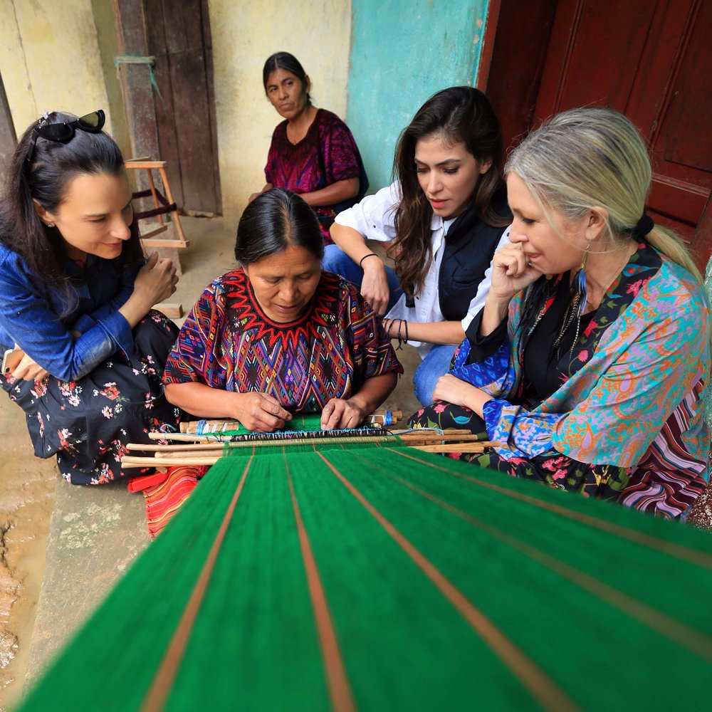 Marianne and Carmen observe the work of a local artisan in Guatemala.