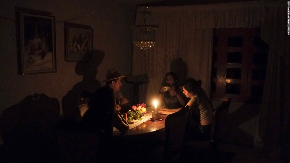 A family sit at a candle lit table in the state of Barinas, Venezuela. Food preparation, healthcare and survival is made difficult / Photo: cnn.com