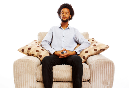 young man sitting meditating in comfy chair on white