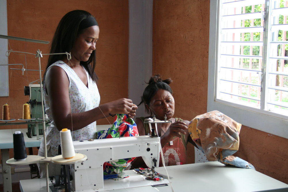 Two women finish sewing shoulderbags at the Learning Center, Cruz Verde, as part of RECLAIM women's sewing microenterprise