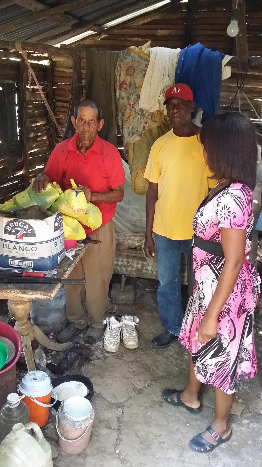 Elderly man in Cruz Verde receiving Health Fund support from Julito and Nina, two SIP program coordinators