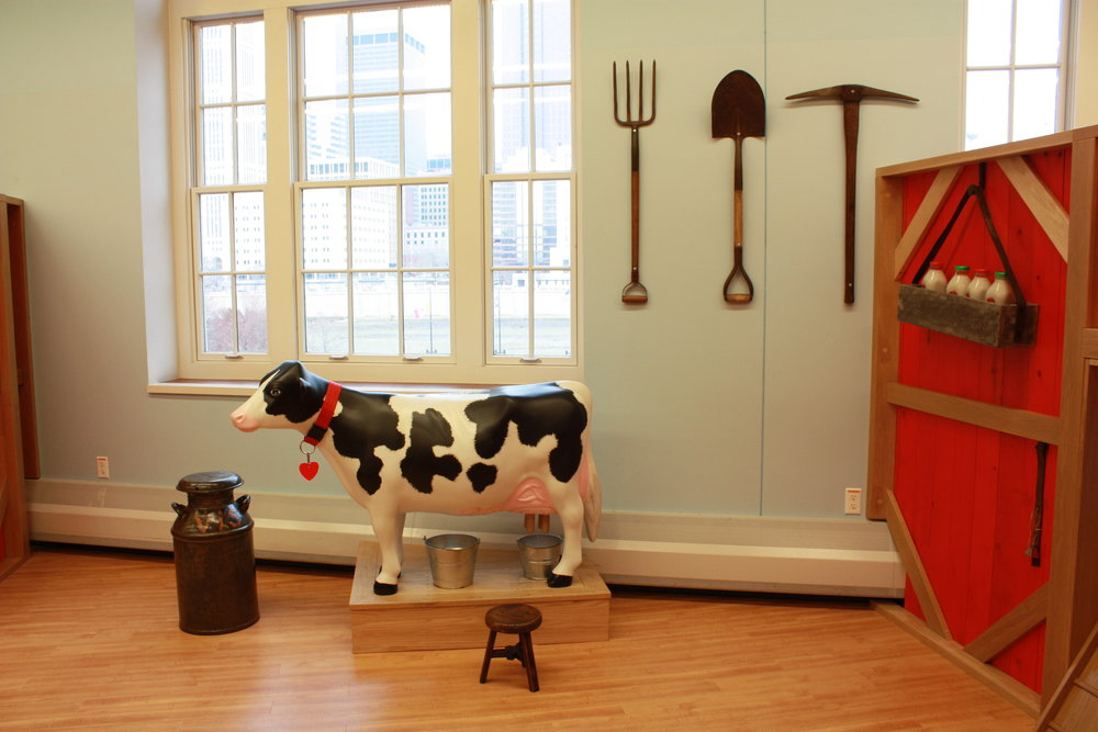 Pretend to milk the cow and observe real objects like milk can, bottles, fork and shovel.