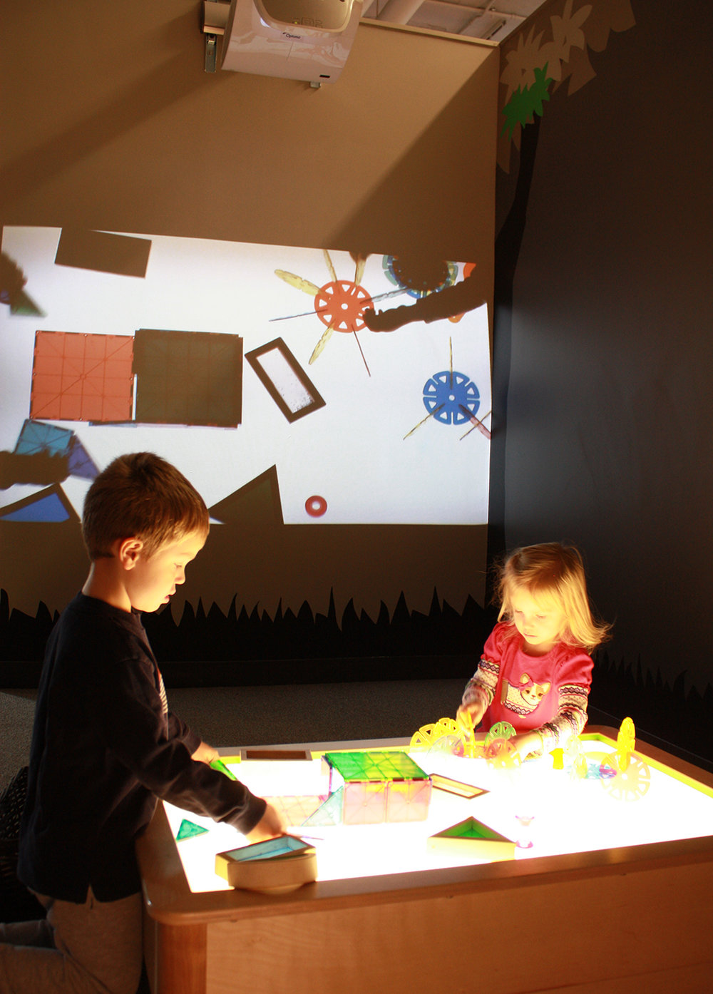 Light table and projection. The designed light table enables children to interact with shapes, color and composition over its surface. At the same time an overhead camera records live movement for it to be projected on the wall.