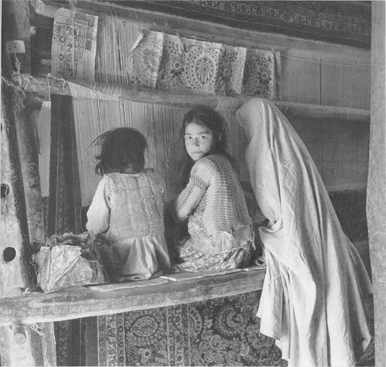 Girls weaving a Persian rug in Hamadan, Iran, circa 1920