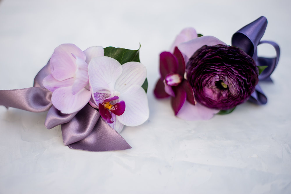 "These are examples of my ""cuff"" corsages.  They are wrapped in the ribbon color of the wedding and finished with delicate blooms and a small bow. Photography by Leandra"