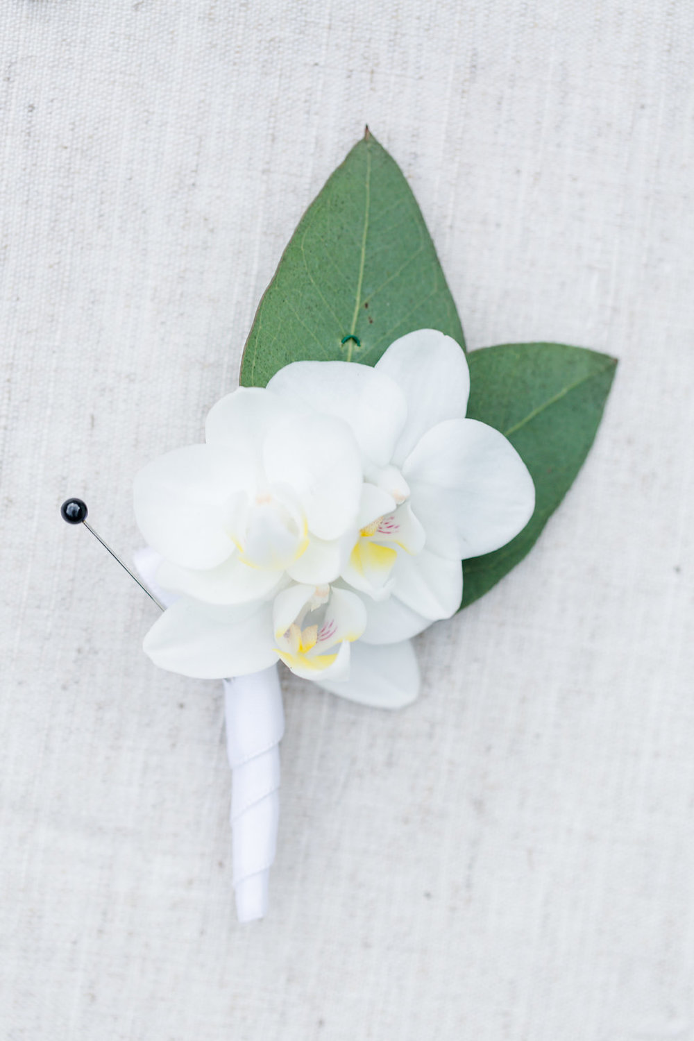 Triple mini Phaleanopsis boutonniere wrapped in ivory satin. Rachel E.H. Photography
