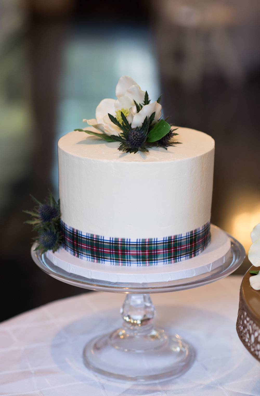 Another shot of the groom's cake adorned with fresh Scottish Thistle and tartan ribbon.