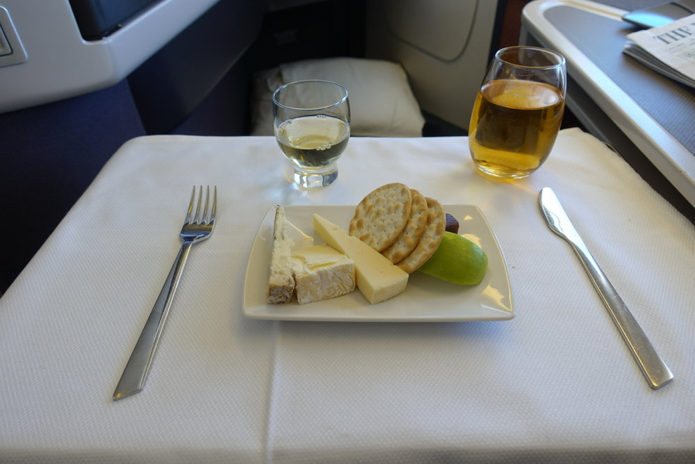 """Cheese, crackers and dessert wine served on board CX418 from HKG --> ICN. """"> Cheese, crackers and dessert wine served on board CX418 from HKG –> ICN.</p> <p>So a few thoughts about Cathay Pacific, as a reference point to compare to Qatar Airways and British Airways later:</p> <p><strong>Mobile app</strong></p> <p>Cathay has improved its mobile app in recent years, but it is still a bit buggy. It has the usual features, such as profile/points accrual information, flight schedules, and the option to book flights through the app (it also wins a huge bonus from me for accepting Apple Pay).</p> <p>The app also provides mobile boarding passes, which is becoming standard and is a feature I use almost every time I fly Cathay. Checking in via the app and downloading a boarding pass without having to speak to a single employee at the airport is true bliss.</p> <p><strong>Lounges</strong></p> <p>Frequent travelers have their favorite lounges, and CX has four of them at Hong Kong International Airport. The newest and flashiest is The Pier, near gate 60. It is absolutely huge, has CX's famous noodle bar (dan dan noodles FTW), a long bar, hot and cold buffet, and a quaint little coffee stand. Almost all seats have electrical outlets and USB ports to charge devices.</p> <p>The Wing is near immigration and is, therefore, the most popular. It also has a noodle bar and long bar but is often extremely crowded. The Bridge is probably my second favorite, and offers a lot of bread-based dishes like pizza, sandwiches, and paninis, while The Cabin is a darker lounge with fewer food options, but is well-known for its fruit smoothies.</p> <p><img src="""