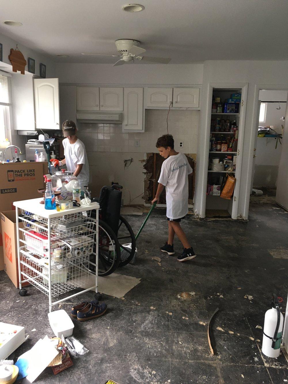 Volunteers sweep the floor after most of the debris has been removed.
