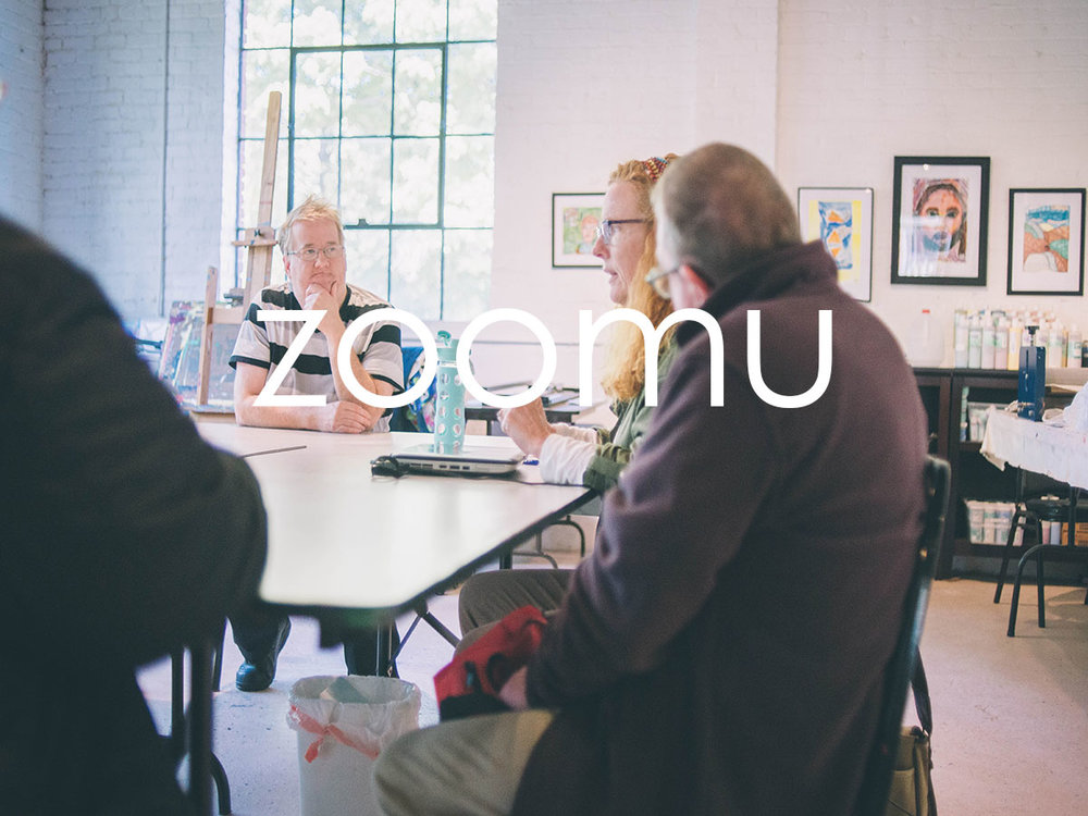 image of multiple individuals having a discussing at a table, in a brightly lit area. One individual is speaking, as the other are listening, consider their words. The word 'zoomu' is overlaid in white on the image.